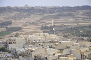 Yellow-greyish Globigerina limestone in buildings as far as the eye can see. The image is taken in Gozo's capital, whose name in Maltese is Ir-Rabat, but was renamed to Victoria to suck up to a certain Queen. In the background, the mighty Ta'Pinu cathedral.