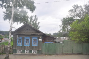 "Classic Kungur house: brown timber walls and colorful window sills. The sign says ""Gagarin Street"", named after Yuri Gagarin, the first man to fly in space."