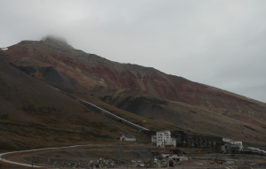 "Pyramiden - the mountain and the mine works. The long tube up from the buildings protected the lift for mine workers to the mine entrance higher in the mountainside. A necessity in the dark Svalbard winter! The dark coal dumps mark the location of the coal seam itself, and above them are the interchanging white anhydrite and red sandstones of the Billefjorden group. Note how the sand wedges out to the right, and thickens to the left, towards the main graben border fault, just outside the image. The nearly ever-present cloud on the top hides the ""hat"" of hard limestone."
