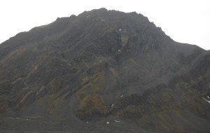 """Mediumfjellet, seen from the sea on a grey Svalbard autumn day. This image shows the two """"horses"""", the slices of hard Permian rocks shuffled upon each other, greased by anhydrite and soft Triassic shale. The more irregular piece of rock in the center of the image is a Cretaceous intrusion, which joined just in time to get on the ride."""