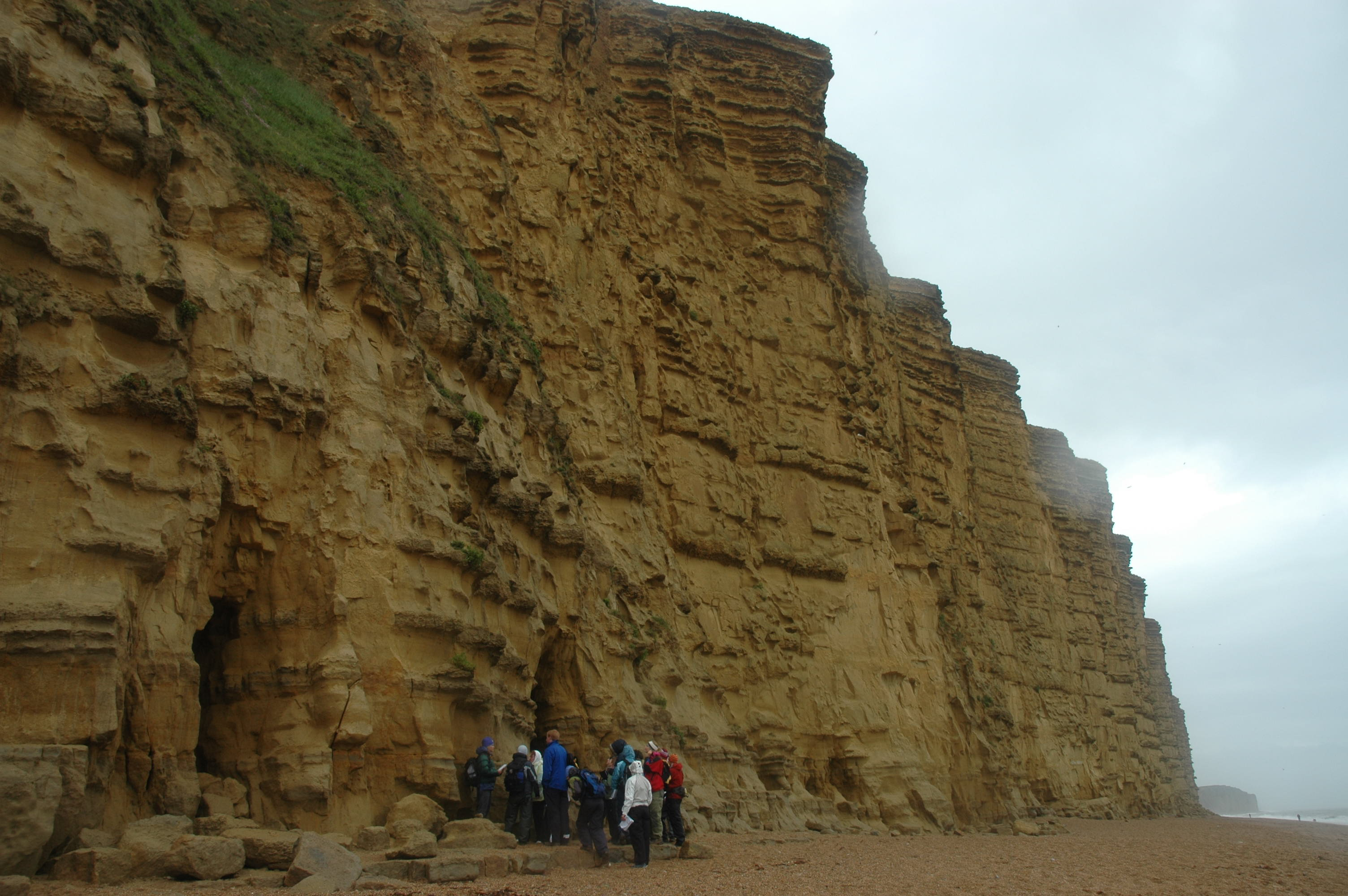 Geology students for scale at the base of the cliffs at West Bay.