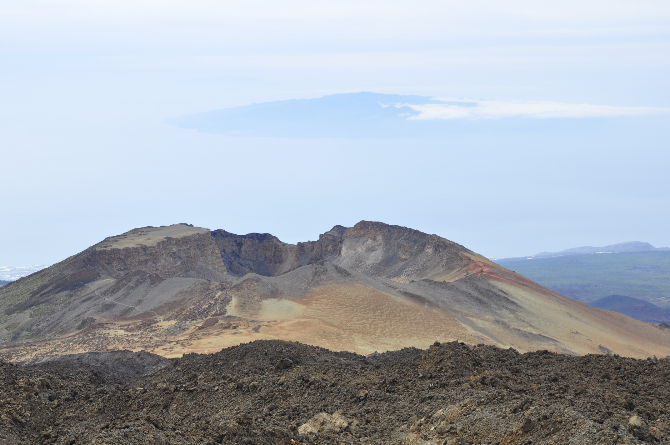Pico Viejo crater, With the remnants of the lava lake, and La Gomera far away and below.